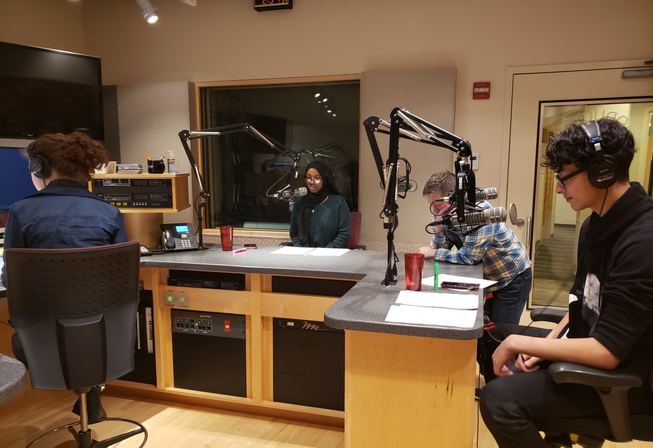 caption: RadioActive youth producers (left to right) Simone St. Pierre Nelson, Marian Mohamed, and Antonio Nevarez record the first youth-produced on-air showcase in December 2019 while RadioActive mentor Kyle Norris looks on.