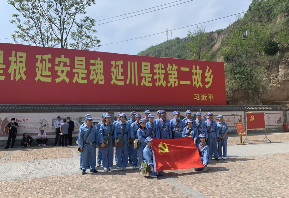 """caption: Tourists dressed up as People's Liberation Army soldiers pose in Liangjiahe village, where a teenage Xi Jinping spent seven years doing hard labor. Today the village is a popular red tourism site. The sign displays a quote from Xi: """"Liangjiahe is where my roots are, and my soul. It is my second home."""""""