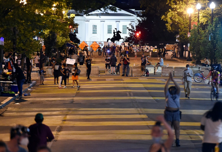 caption: Protesters gather on Friday night at Black Lives Matter Plaza in front of the White House and the statue of former President Andrew Jackson, which is protected by a fence and concrete blocks.