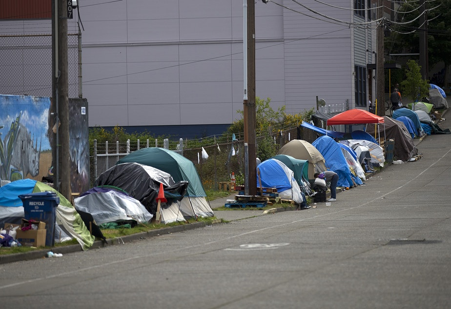 caption: Tents line South Weller Street near the intersection of 12th Avenue South on Tuesday, May 19, 2020, in Seattle.