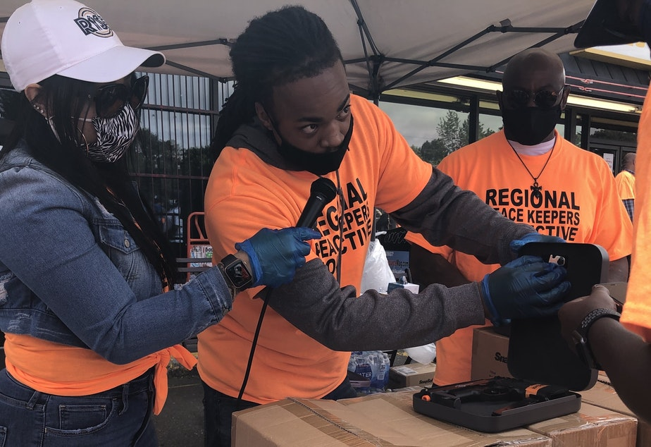 caption: Aaron Knox, center, with the YMCA's Alive & Free program, demonstrates how to use a firearm lockbox at the June 4, 2021 kickoff of King County's Regional Peacekeepers Collective in Skyway.