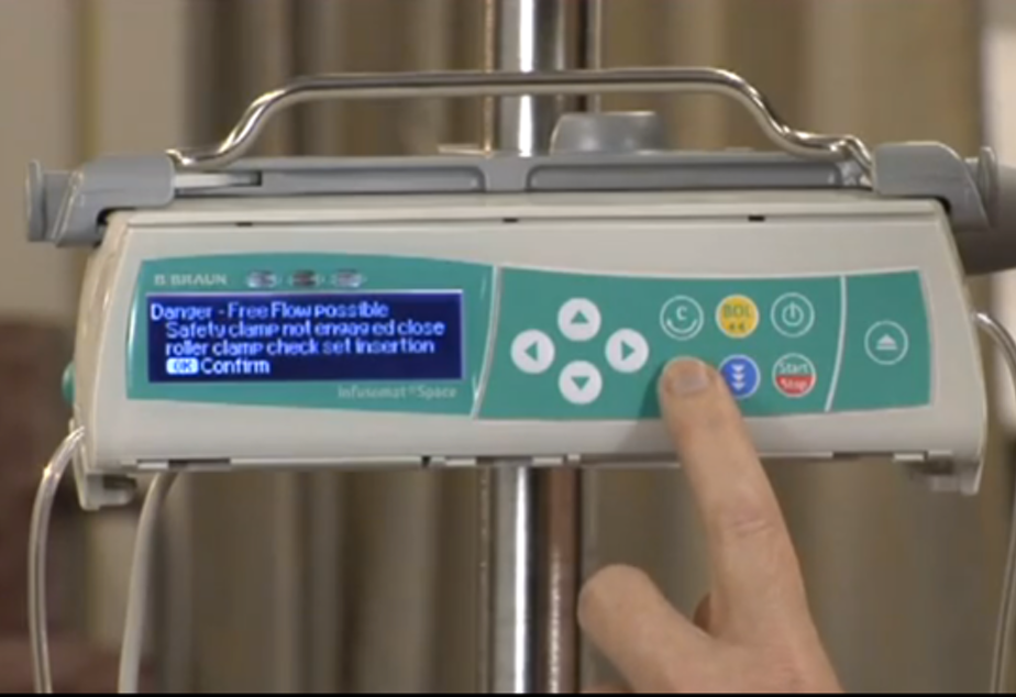 "caption: A screenshot from an Infusomat training video warns of the danger of a ""free flow"" of drugs pouring from the machine if loaded improperly."