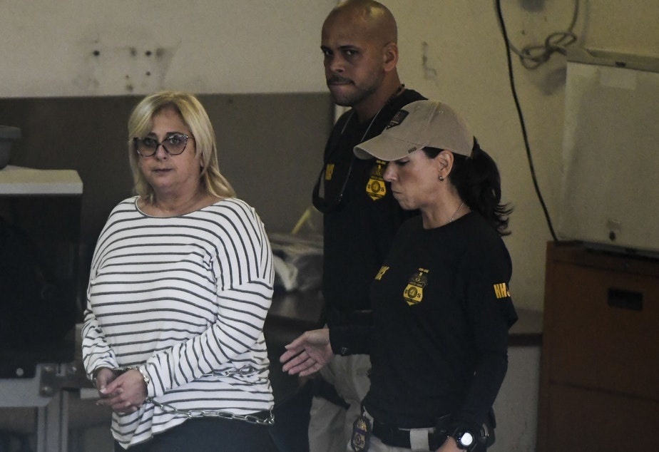 caption: Federal agents escort former Puerto Rico Health Insurance Administration head Ángela Ávila-Marrero, who was arrested on Wednesday as part of a corruption investigation that resulted in an indictment against six defendants.