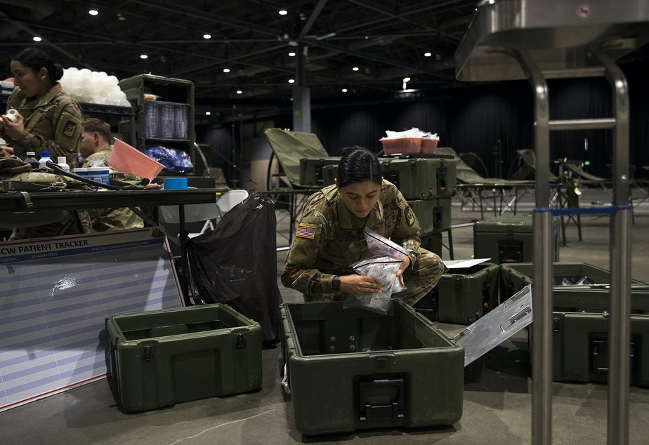 caption: U.S. Army soldier Sara Dulmaine sorts medical supplies in the ICU area of a 250-bed military field hospital for non COVID-19 patients being deployed by soldiers from the 627th Army Hospital from Fort Carson, Colorado, as well as from Joint Base Lewis-McChord on Tuesday, March 31, 2020, at the CenturyLink Field Event Center in Seattle.