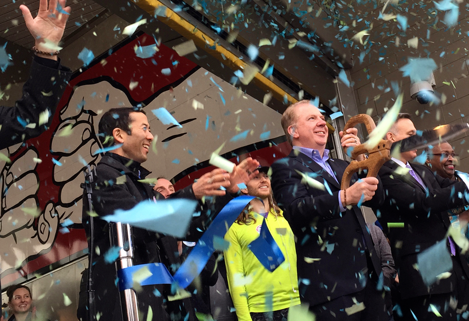 caption: Seattle Mayor Ed Murray (holding giant scissors) and other officials celebrate the opening of a light-rail station on Capitol Hill.