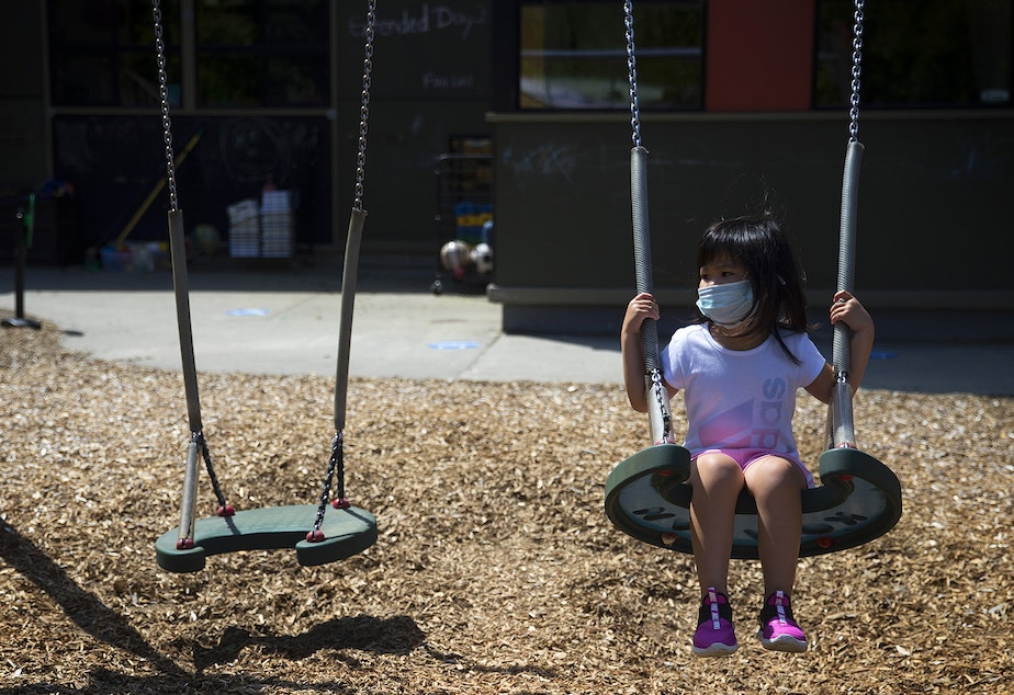 caption: A student at the Denise Louie Education Center swings on a swing set after collecting flowers on a walk with teacher Margarita Arias on Thursday, July 16, 2020, on the playground along Beacon Avenue South in Seattle.