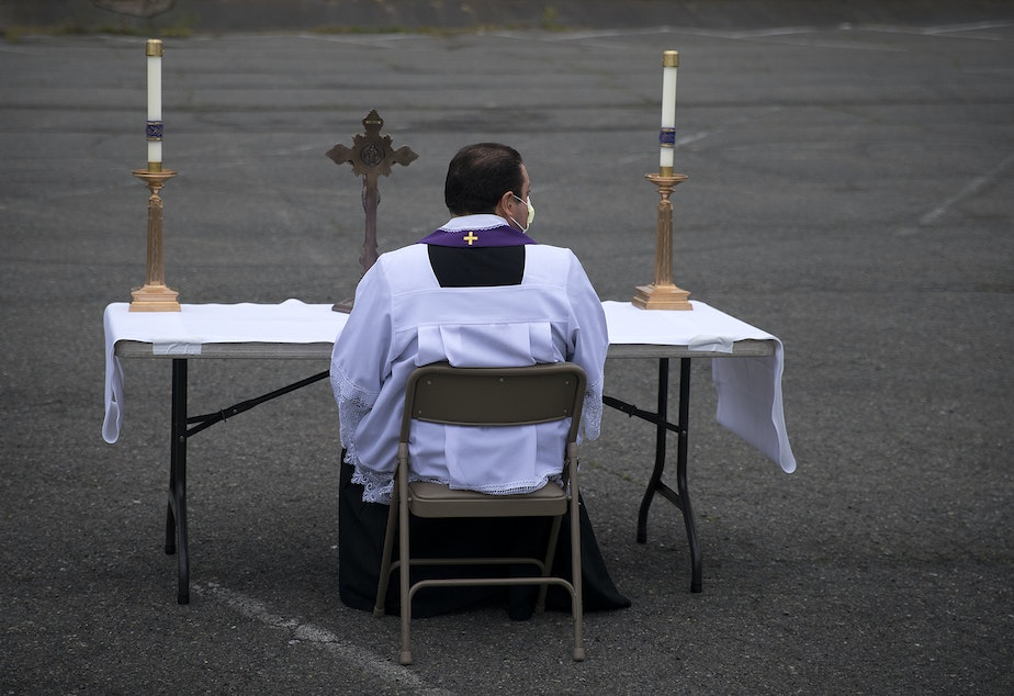 caption: Father Jose Alvarez waits for people to arrive for walk and drive through confessions on Friday, April 24, 2020, in the parking lot at Holy Family Roman Catholic Church in White Center.
