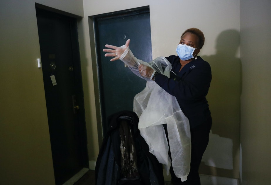 caption: In this Thursday, April 23, 2020 photo, Ruth Caballero, a nurse with The Visiting Nurse Service of New York, puts on personal protective equipment before entering a patient's apartment as she makes her rounds in upper Manhattan in New York. (John Minchillo/AP Photo)