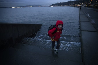 Ely Thomas, 7, runs from water spilling over a set of stairs that normally lead to the beach during a King Tide at Alki Beach Park on Friday, January 5, 2018, in West Seattle.