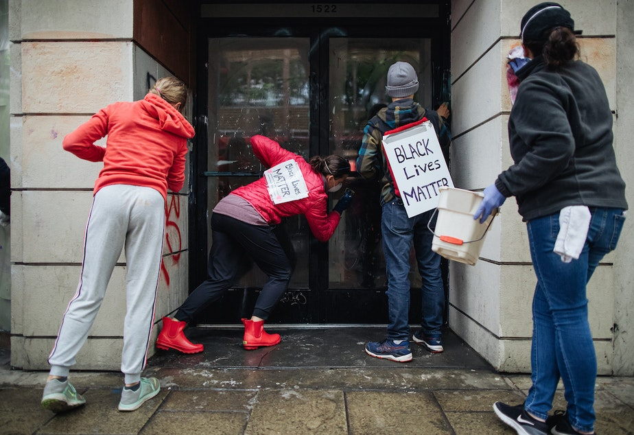 """caption: People cleaning up on Sunday morning in downtown Seattle wore signs that read """"racism caused this mess"""" and """"Black Lives Matter."""""""