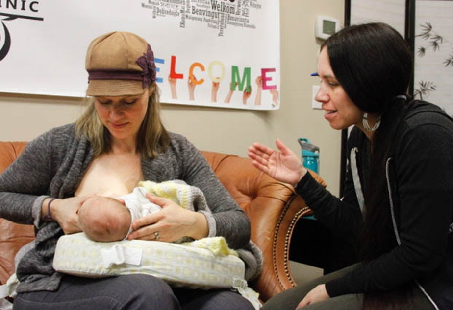 caption: Lactation consultant Camie Goldhammer helps 5-week-old Darius latch onto his mother, Carole Gibson-Smith. Goldhammer, a social worker by training, focuses on breastfeeding in communities of color, particularly in Native communities.