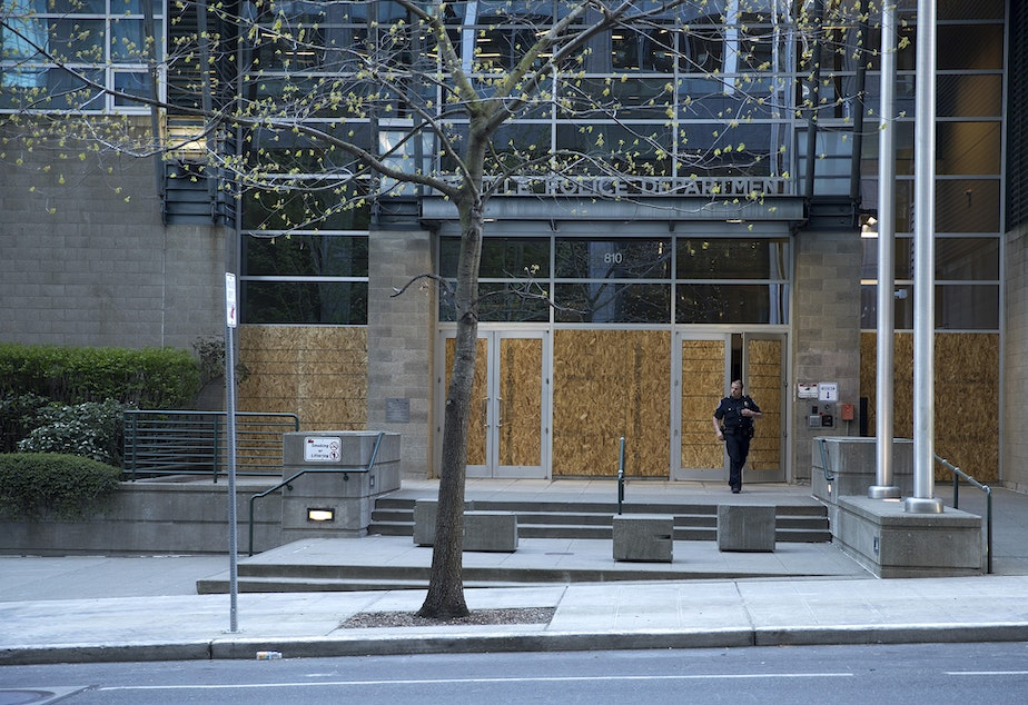 caption: A Seattle police officer exits the police department's boarded-up West precinct building following the reading of the guilty verdict in the trial of Derek Chauvin for the murder of George Floyd, on Tuesday, April 20, 2021, along Virginia Street in Seattle.