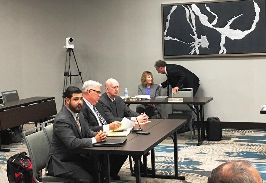 caption: Michael Herrera, left, and Bradley Kruger, center, of the National Rifle Association at a Washington State Gambling Commission Meeting