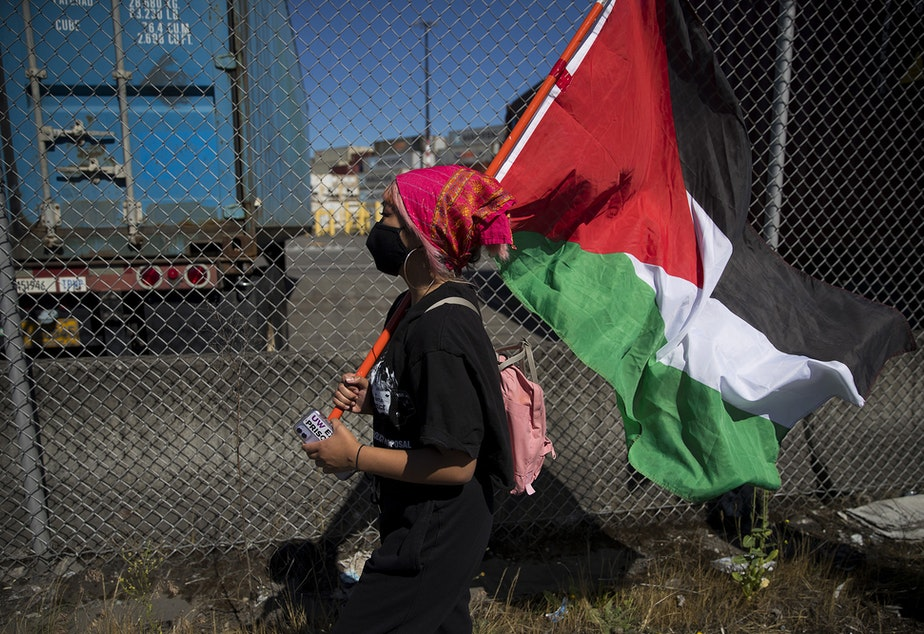 caption: Jasmine Fernandez marches alongside Palestinian activists and allies before blocking an intersection in protest of the Israeli Zim San Diego Vessel on Thursday, June 17, 2021, at the Port of Seattle.