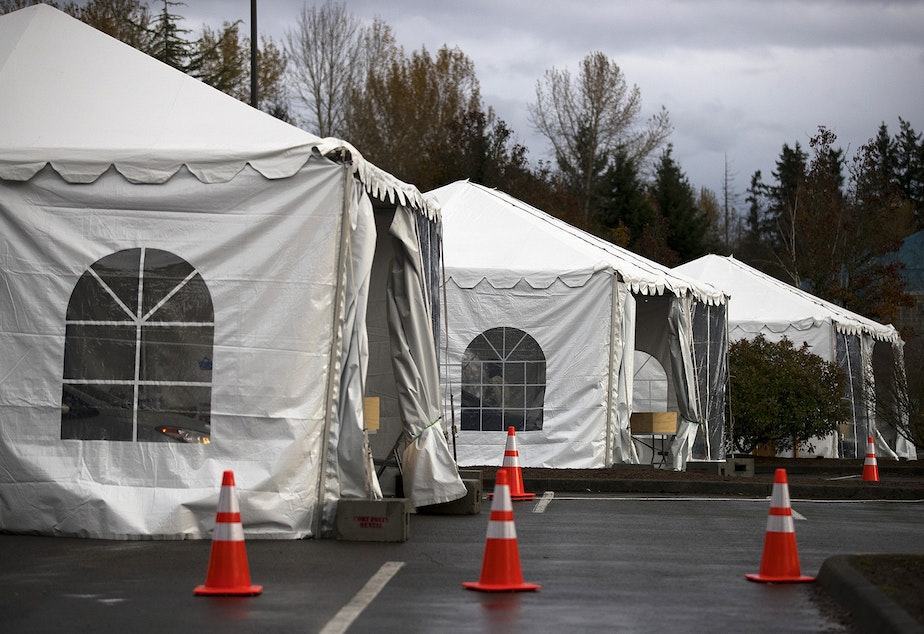 caption: Tents set up for drive-through Covid-19 testing are shown on Wednesday, November 18, 2020, in the parking lot of the Weyerhaeuser King County Aquatic Center along Southwest Campus Drive in Federal Way.