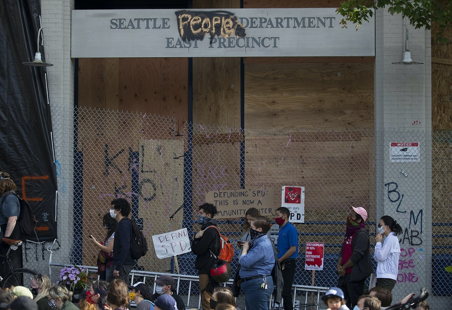 caption: A crowd gathers at the intersection of 12th Avenue and East Pine Street, outside of the Seattle Police Department's East Precinct building, in the 'Capitol Hill Autonomous Zone', also known as CHAZ, on Wednesday, June 10, 2020, in Seattle.
