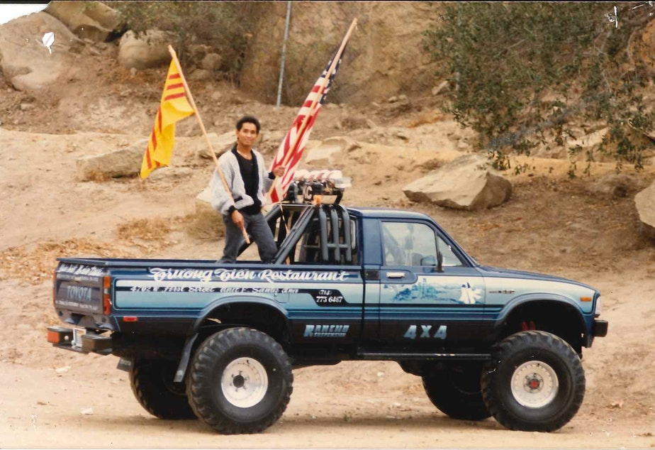 caption: Quang Adam Nguyen, Angela's dad, holding the South Vietnamese and American flags.