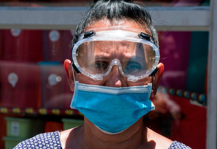 caption: A woman wears a face mask and goggles as a preventive measure against the new coronavirus.
