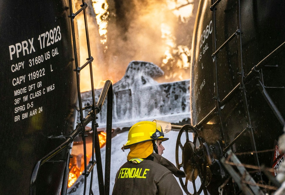 caption: A firefighter works as a derailed train carrying crude oil burns on Dec. 22 in Custer, Washington.