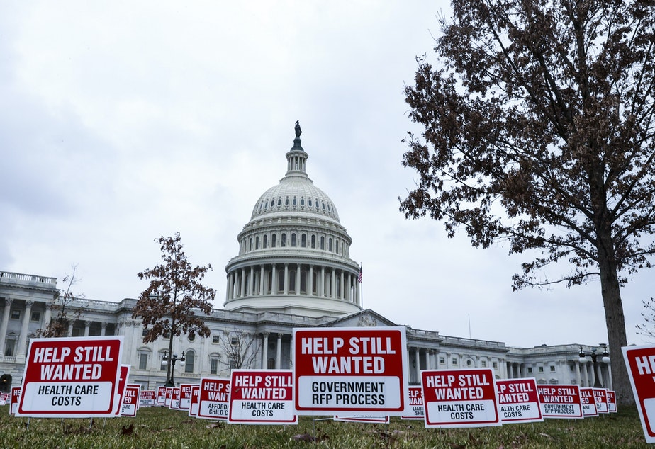 "caption: Signs reading ""Help Still Wanted"" were positioned on the lawn outside the U.S. Capitol on Jan. 5. The House Budget Committee meets Monday afternoon, setting up a vote on the coronavirus relief package by the end of the week."