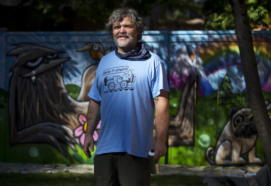 caption: Ryan Henry Ward stands for a portrait in front of a mural that he is working on in the backyard of a home on Wednesday, September 8, 2021, in Shoreline.