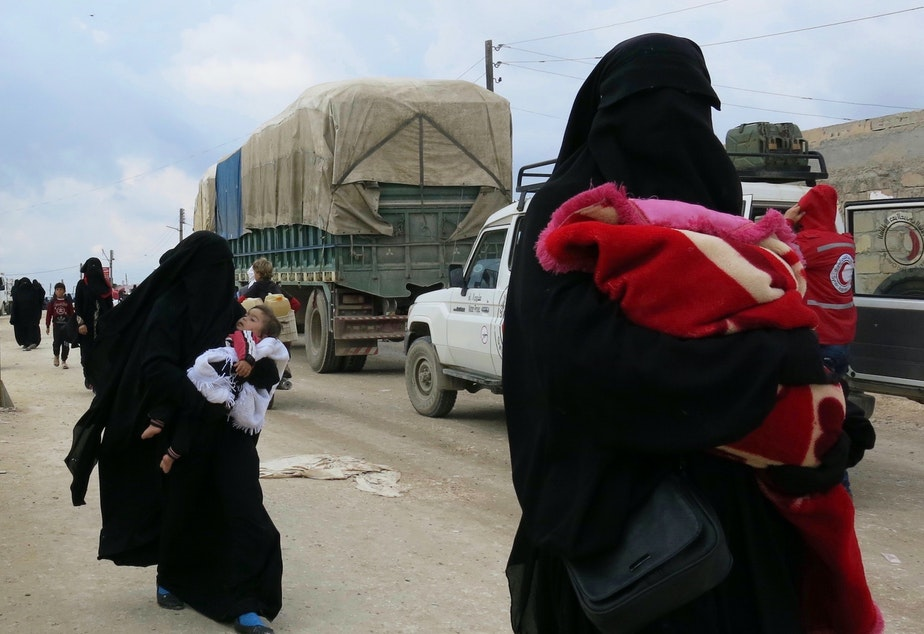 caption: Women carry children near the al-Hol camp in Syria's Kurdish-majority region of Rojava. The camp is filled with more than 72,000 people — most of them women and children who came out of the last ISIS-held territory.