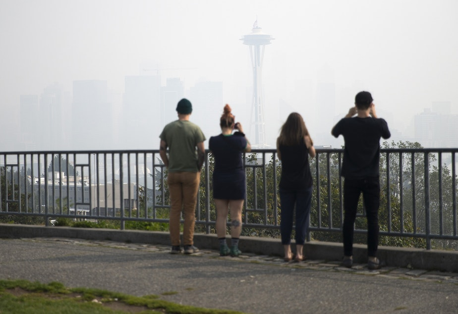 caption: People photograph a smoke covered downtown Seattle as a massive plume of smoke from wildfires burning in California and Oregon made it's way into the area on Friday, September 11, 2020, at Kerry Park in Seattle.