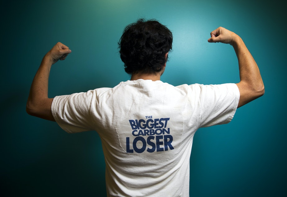 KUOW's Juan Pablo Chiquiza poses in a Biggest Carbon Loser t-shirt.