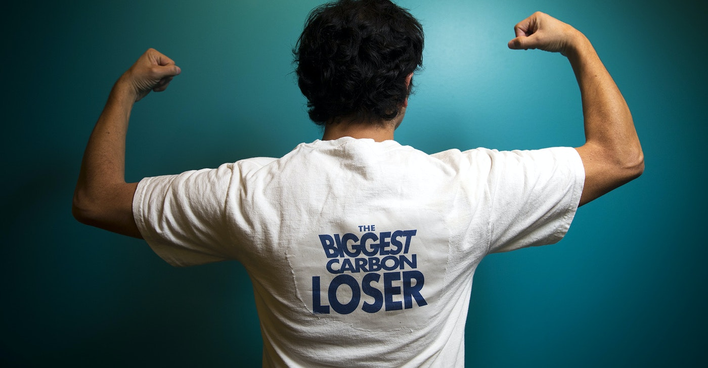 caption: KUOW's Juan Pablo Chiquiza poses in a Biggest Carbon Loser t-shirt.