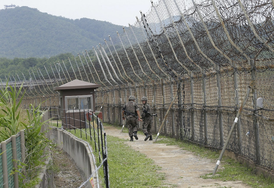caption: South Korean soldiers patrol while hikers visit the DMZ Peace Trail in the Demilitarized Zone in Goseong, South Korea. A defector from North Korea was apprehended in Goseong last week after evading South Korean guards for hours.