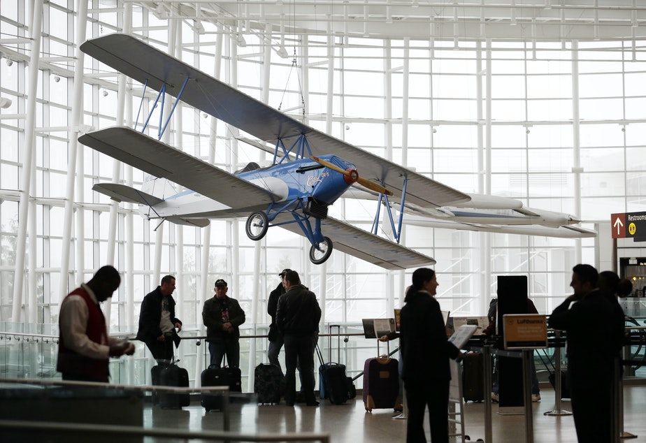 caption: In this photo taken Tuesday, Oct. 22, 2013, a biplane hangs from the ceiling of the Gina Marie Lindsey Arrivals Hall at Seattle-Tacoma International Airport in SeaTac, Wash.