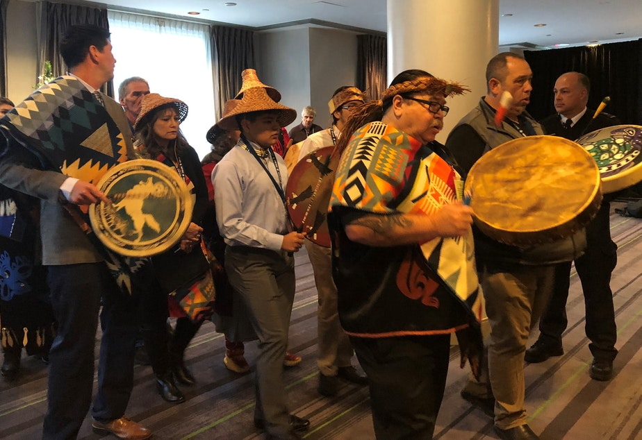 "caption: Representatives of Washington tribes perform a ""paddle song"" at the start of a 2018 hearing in Victoria, B.C., to oppose the Trans Mountain Pipeline"