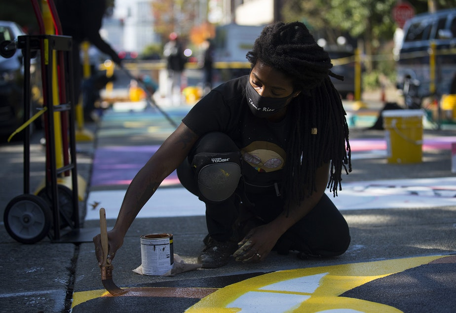 caption: Aramis O. Hamer paints the letter V in the Black Lives Matter street mural on Friday, October 2, 2020, on E. Pine Street in Seattle.