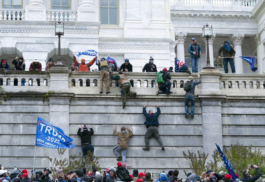 caption: In this Jan. 6, 2021 file photo rioting supporters of President Donald Trump climb the west wall of the the U.S. Capitol in Washington. Historians say Trump's legacy and his electoral undoing will be largely shaped by rhetoric aimed at stirring his largely white base that tugged at the long-frayed strands of race relations in America.