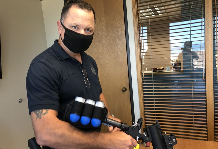 caption: Tim Collings with the Everett Police Department demonstrates use of a launcher that fires 40mm non-lethal rounds. They've stopped using the launchers in the wake of a new state ban on large-caliber ammunition.