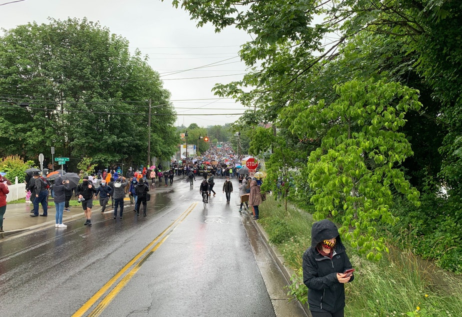 caption: Marchers approach South College Street as they proceed on 23rd Avenue South. The silent protest organized by Black Lives Matter Seattle-King County drew thousands.