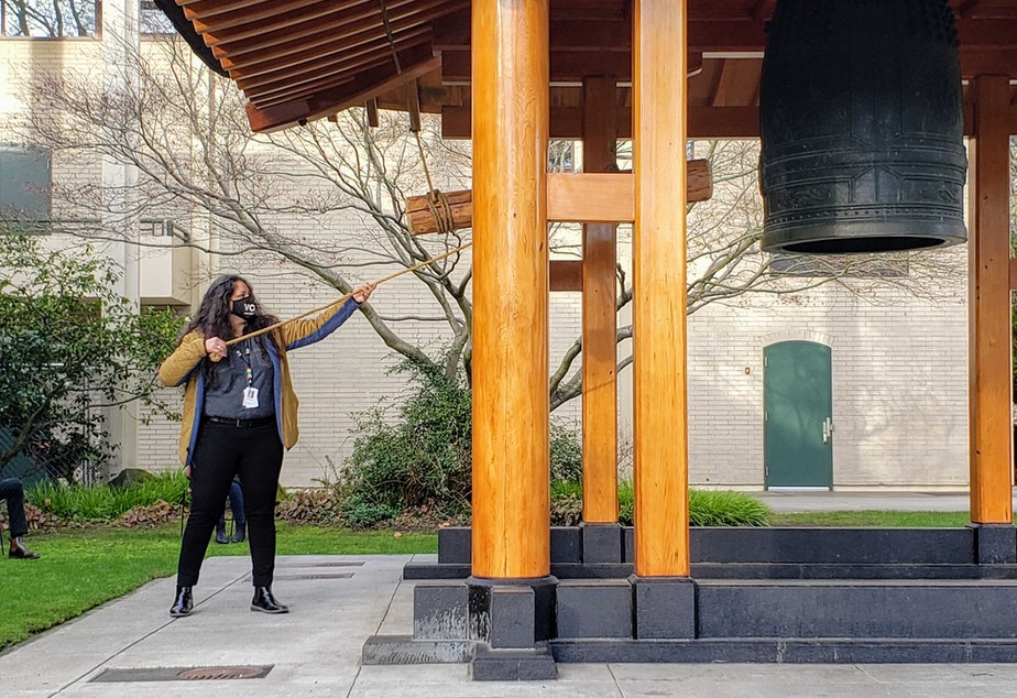 caption: Esther Lucero, of the Seattle Indian Health Board, rings The Kobe Friendship Bell in Seattle Center on Tuesday, January 19, 2021.
