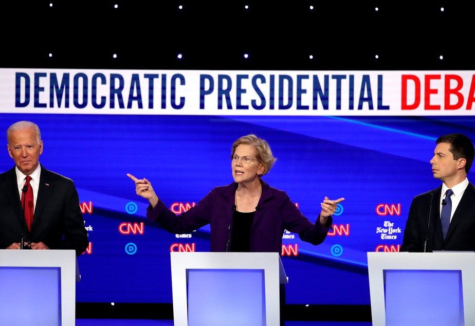 caption: Left to right, former Vice President Joe Biden, Massuchusetts Sen. Elizabeth Warren and South Bend, Ind. Mayor Pete Buttigieg react on stage during the Democratic Presidential Debate at Otterbein University.
