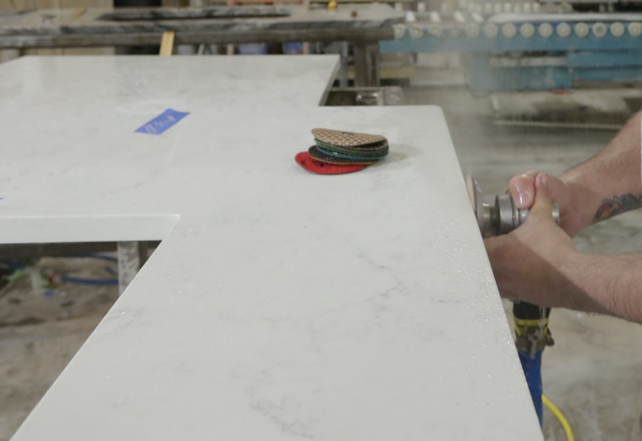 """caption: A worker polishes the edge of a kitchen countertop cut from a slab of quartz, an """"engineered stone"""" that can produce harmful silica dust when cut, ground or polished."""