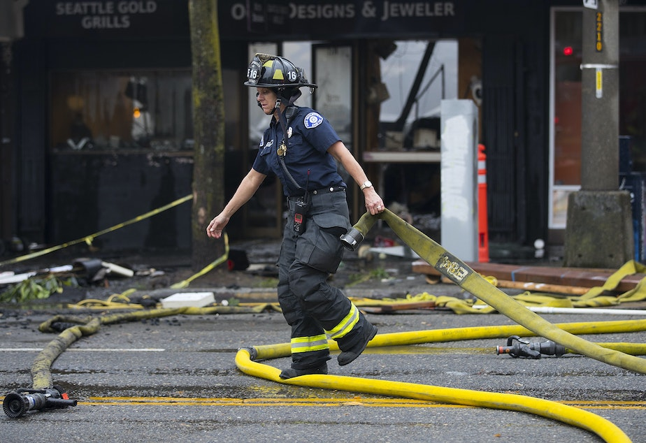 caption: Firefighters work to put out a fire on Monday, October 7, 2019, near the intersection of NW Market Street and 24th Avenue Northwest in Seattle.