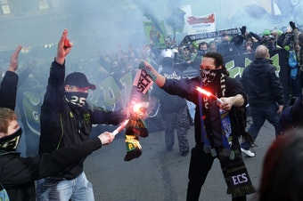 Seattle Sounders fans burn a Portland Timbers scarf during the 'March to the Match' before an MLS soccer match, Saturday, March 16, 2013, in Seattle.