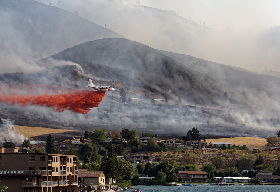 caption: A plane flies over Chelan within hours of a wildfire starting on Aug. 14, 2015. Sunbathers on holiday watched as the fire effort took hold.