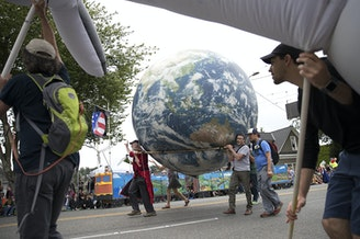 Parade-goers carry a blow-up planet Earth while marching in the Fremont Solstice Parade.