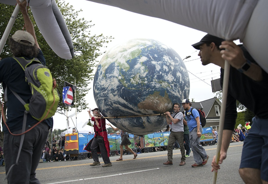 caption: Parade-goers carry a blow-up planet Earth while marching in the Fremont Solstice Parade.