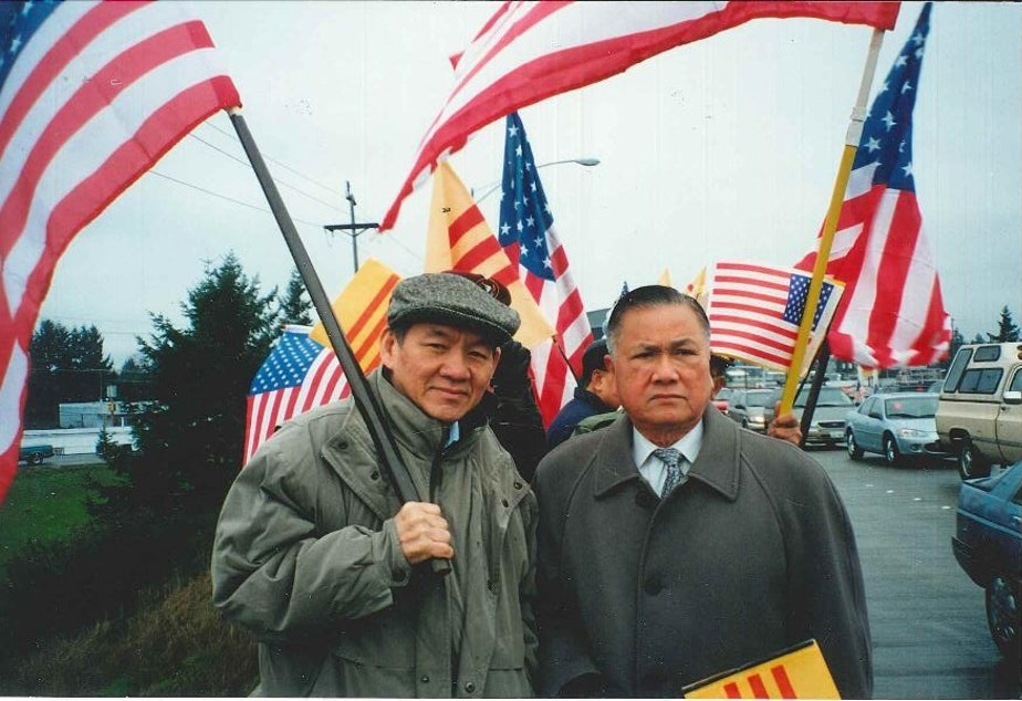 caption: Thanh's father, Duc Tan, holds the American flag and stands next to Dr. Dung Nguyen, president of the Vietnamese Community of Pierce County, at a political rally in this undated photo.