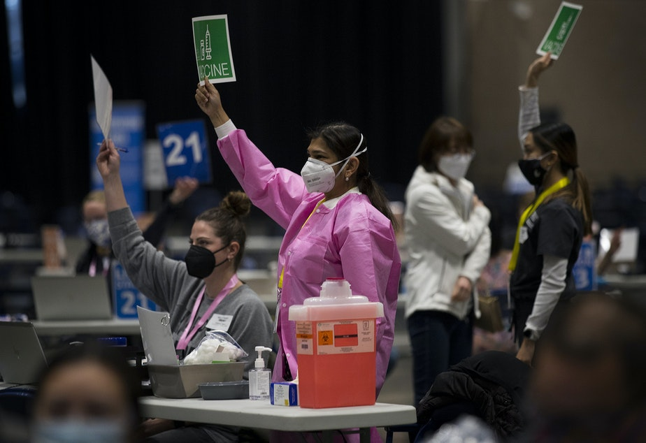 caption: Volunteer Dr. Aditi Agardwal, center in pink, raises a piece of paper indicting that she needs more vaccine on Saturday, March 13, 2021, at the new civilian-led mass Covid-19 vaccination site at Lumen Field Event Center in Seattle. More people will be eligible for the vaccines as of March 31, Gov. Inslee announced Thursday.