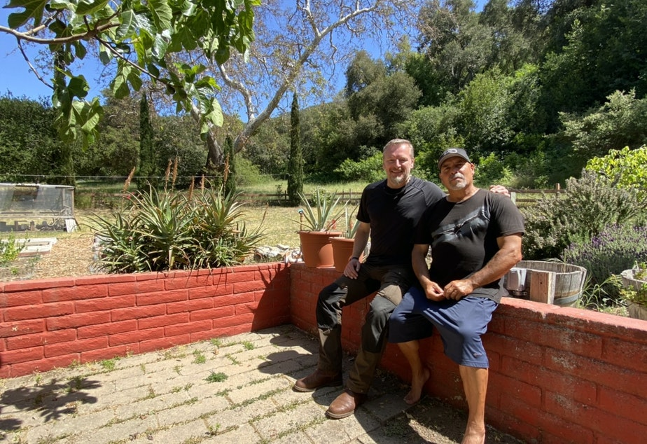 caption: Host Chris Morgan (left) sits in the backyard of Anthony Prieto (right) who advocates for hunters to use lead free ammunition to protect condors.