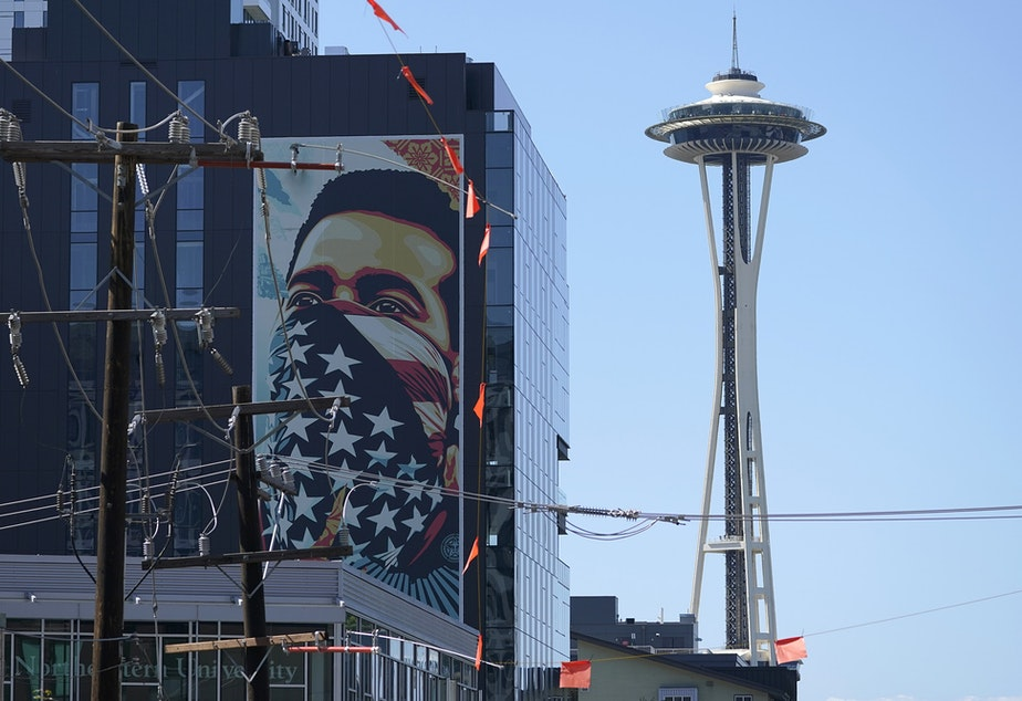 caption: The Space Needle is shown, Thursday, Sept. 2, 2021, in Seattle, near a painting by Shepard Fairey of a person masked with a U.S. flag that is based on a photo taken by Ted Soqui during a Black Lives Matter protest, that is displayed on a building.