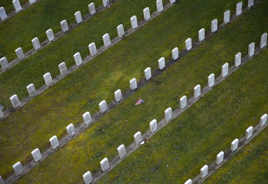 An American flag is shown between rows of headstones in the Veterans section on Thursday, March 1, 2018, at Evergreen Washelli Cemetery in Seattle.