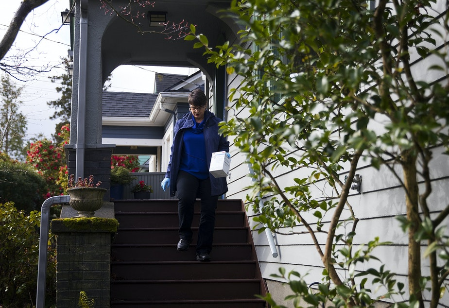 caption: Dawn Lum, with the Seattle Mask Brigade, collects a donated box of masks from a porch on Wednesday, April 1, 2020, in Seattle.